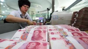 A teller counts yuan banknotes in a bank in Lianyungang, China, August 11,